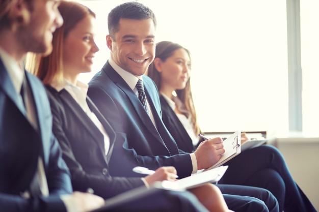 hombre-de-negocios-sonriente-en-una-convencion_1098-571